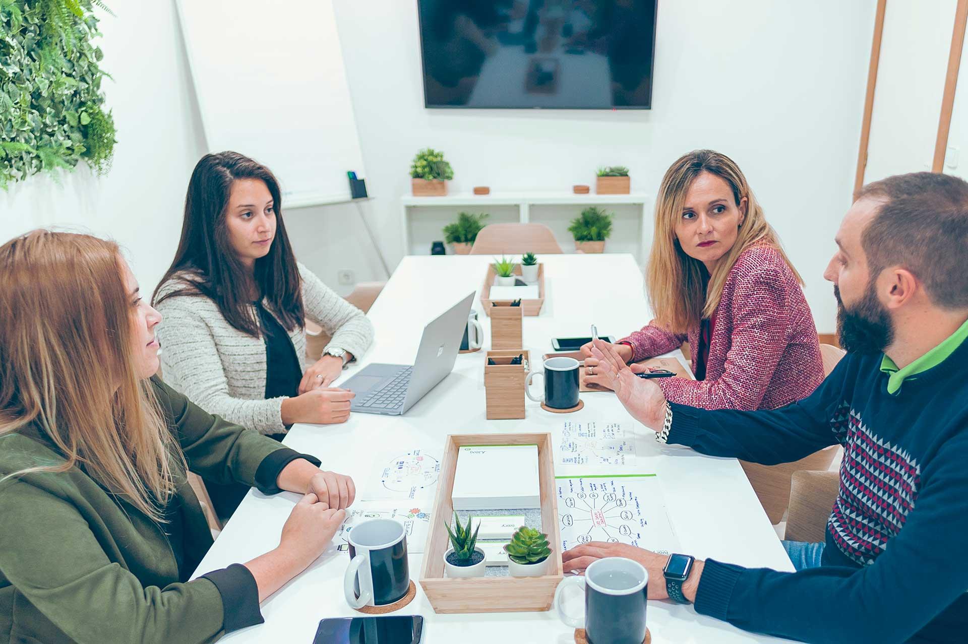 Integrantes del equipo de Ivory Soluciones reunidos con un cliente en la sala de reuniones