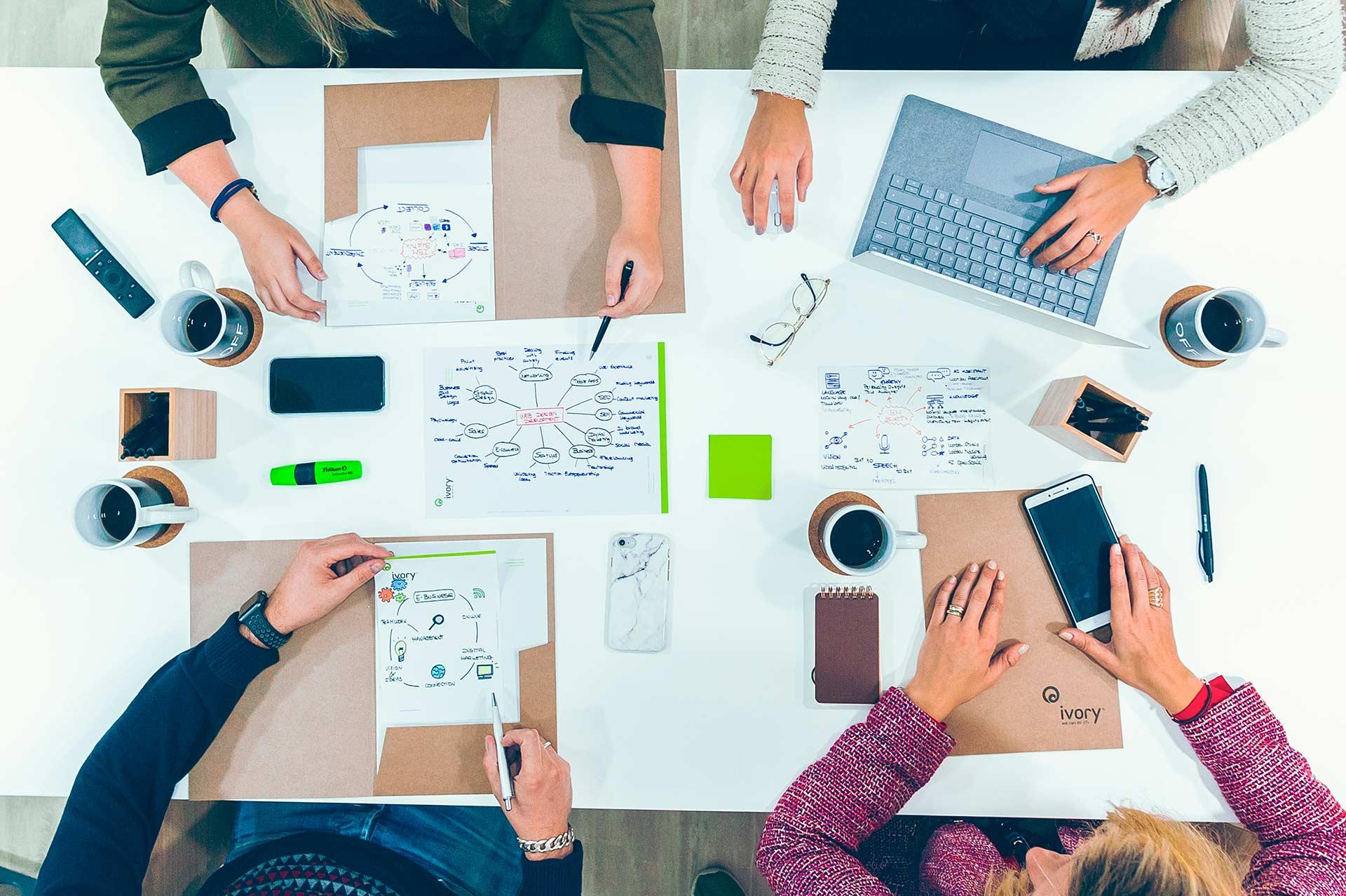 Plano cenital en la sala de reuniones de Ivory Soluciones, con el equipo compartiendo ideas